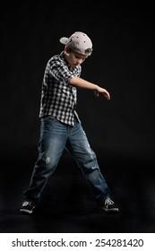 little break dancer showing his skills on black background. Hip hop dancer boy performing isolated over dark background