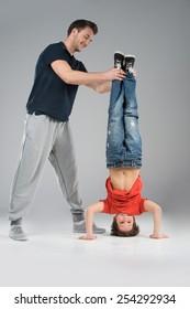 little break dancer showing his skills on grey background. man helping dancer boy performing isolated over dark background