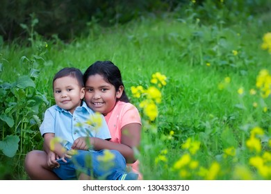 A little brother being held by his big sister, sitting together in a green field during spring.