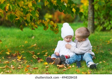 The little brother cares for the baby sister in the autumn city park.
