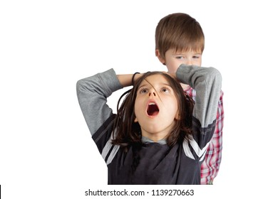 A little brother pulls the hair of his older sister.  He looks sly and mischievous.  She grabs her head with an open mouth look of shock and pain.
