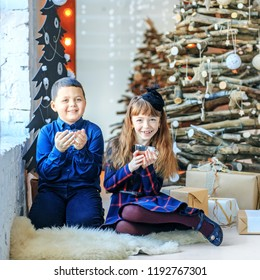 Little brother and sister drink tea and laugh. Square. The boy and the girl. Concept Happy Christmas, New Year, holiday, winter, childhood.