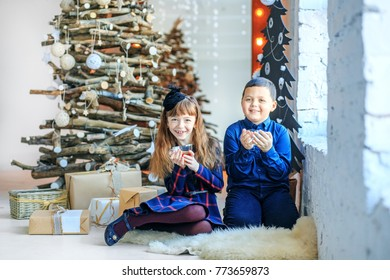 Little brother and sister drink tea and laugh. The boy and the girl. Concept Happy Christmas, New Year, holiday, winter, childhood.