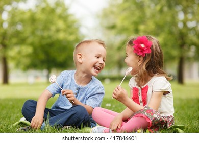 Little brother and sister enjoy lollipops and having fun in the park