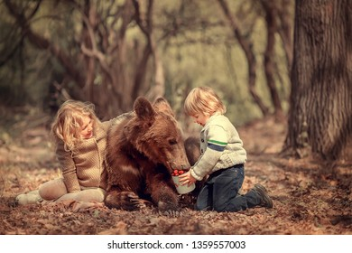 Little brother and sister have met a real bear in the forest and fed him with raspberry. Image with selective focus and toning