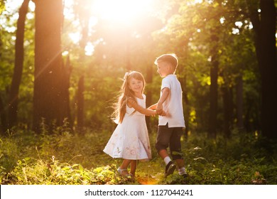 Little brother and sister holding hands and dancing in the park. Happiness   summer holiday vacation concept. Children's friendship
