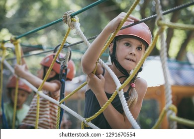 little brother and sister make climbing in the adventure park at the day time. Concept of happy game. Child having fun outdoors.