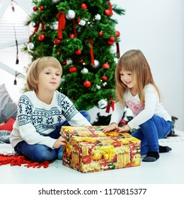 little brother and sister near a Christmas tree with a surprise. Square. The concept of Christmas and New Year.