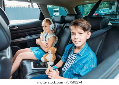 little brother and sister ready for trip on backseats of car