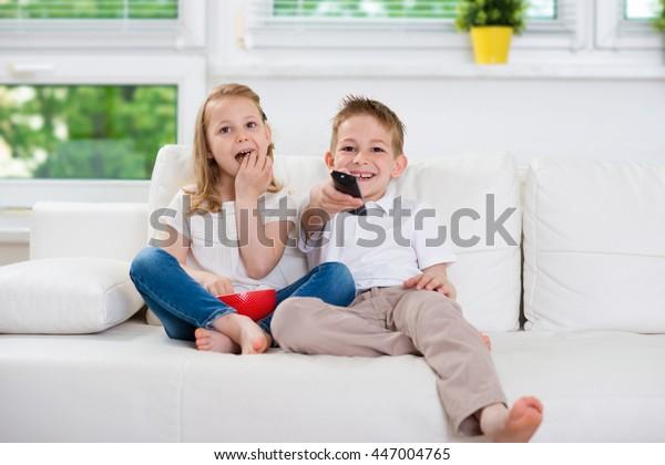 Hermano pequeño y hermana viendo televisión en el sofá
