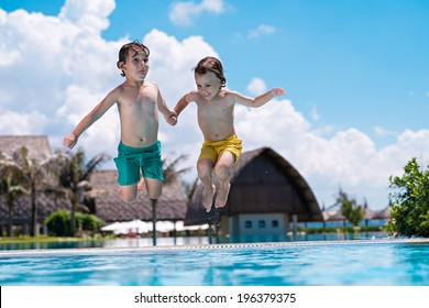 Little brothers jumping into swimming pool while they are holding their hands