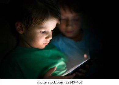 Little brothers playing on tablet at night