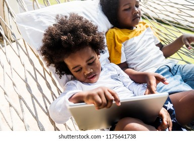 Little brothers using tablet while on holiday