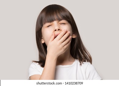 Little brown-haired girl feeling tired or sleepy cover mouth with hand closed eyes yawning isolated on beige studio background, close up face adorable preschool kid suffer from boredom concept image