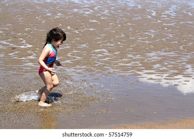 Little brunette girl in pink and blue bathing suit splashing in the water having fun  at New River beach, New Brunswick, Canada