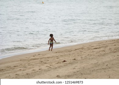 Little brunette girl playing alone on the beach in front of the sea. Ilhabela, Brazil