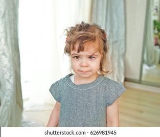 Little brunette girl  posing near window. Girl have crossed eyes and strabismus.