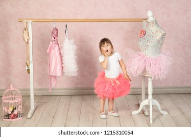a little brunette girl in a white jacket and pink skirt pack is surprised to put his hand to his cheek in the ballet Studio with pink Wallpaper and wooden floor