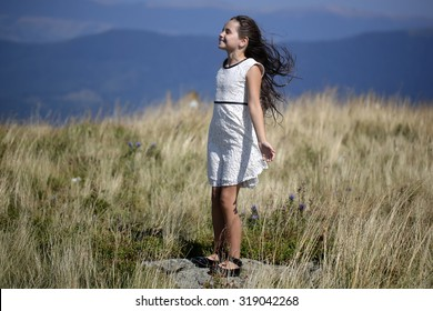 3f2615bf1e2c1 Little brunette girl in white lace summer dress standing in mountain valley  with deep dry spikelet