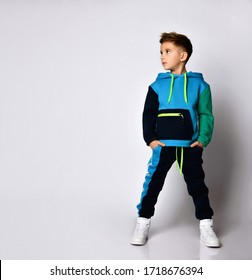 Little brunette kid in colorful tracksuit, sneakers. He put hands in pockets, posing isolated on white studio background. Childhood, fashion, advertising and sport concept. Full length, copy space