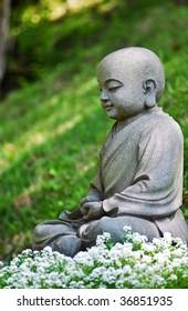 Little Buddha statue in the garden flowers