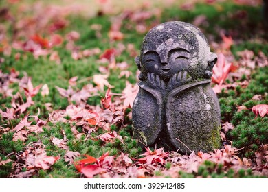 Little Buddha statue on the dry maple leaf floor