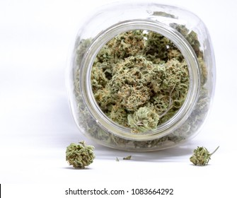 Little buds of cannabis outside a jar with white background