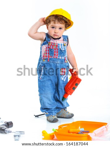 291210b540a Baby boy in a helmet plays in the builder with tools. Isolated over white.  - Image
