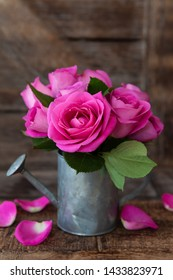 Little bunch of lush pink roses in vintage watering can