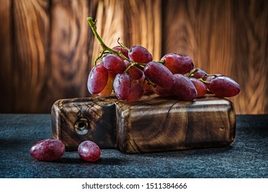 little bunch of rose grape on small vintage carving board and wooden background