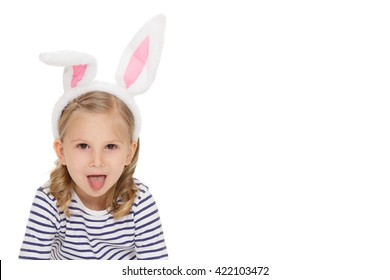 Little bunny. Portrait of an attractive little child wearing bunny ears looking to the camera showing her tongue at the studio isolated on white.