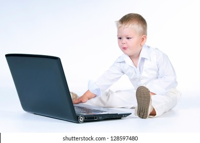 Little business boy in  solid white suit sitting at notebook on a white background