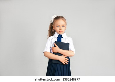 A little business girl hugged the folder with both hands on a gray background. A girl dressed in a white shirt and blue tie with a questioning look.