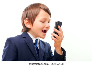 Little businessman. Confident little boy in suit talking emotionally on the phone while standing isolated over white background
