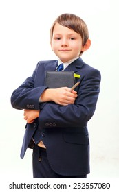Little businessman. Side view image of confident little boy in suit holding a thick notebook while standing over the white background