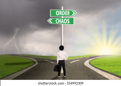 Little businessman standing on the road looking at signpost of order and chaos