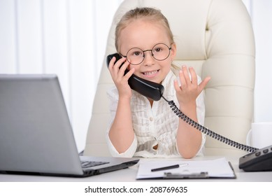 Little businesswoman. Confident little girl in glasses talking on the phone while sitting at the table