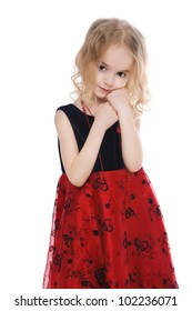 Little calm blond girl in black and red dress isolated on white background