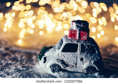 Little car with Christmas gifts on the roof driving through snow. Lights in the background. Wintertime.