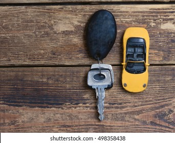 little car and keys on a wooden table.view from above.toned