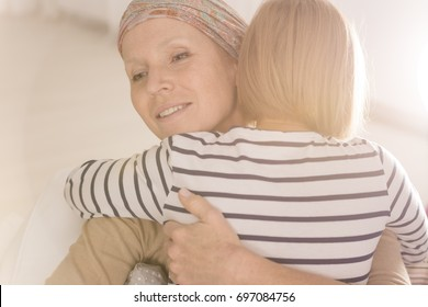 Little caring girl embracing mother suffering from leukemia disease