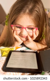 Little caucasian 6-8 years old girl reading a e-book reader in the bed before sleep. Children and tecnology. Education concept