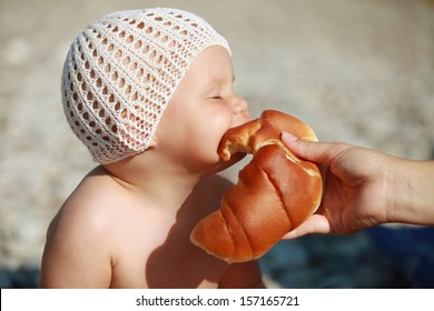Little Caucasian baby eats with pleasure croissant on the beach