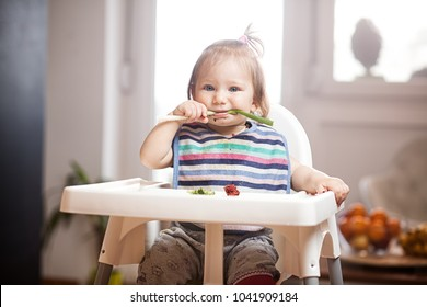 Little caucasian baby girl eating vegetables in a feeder in bright sunny lit room, health raw whole food vegan or vegetarian childhood life, baby led weaning self feeding concept