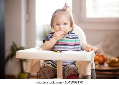"""Little caucasian baby girl eating vegetables in a feeder with a """"excuse me"""" hiccuping look on her face, healthy whole raw vegan or vegetarian childhood life, baby led weaning self feeding concept"""