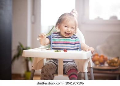 Little caucasian baby girl eating vegetables in a feeder in bright sunny lit room, healthy raw whole vegan or vegetarian childhood life, baby led weaning self feeding concept