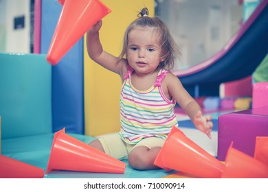 Little Caucasian baby in playground. Little girl playing with toys.