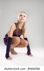 little caucasian blond girl sitting on hunkers and looking up isolated