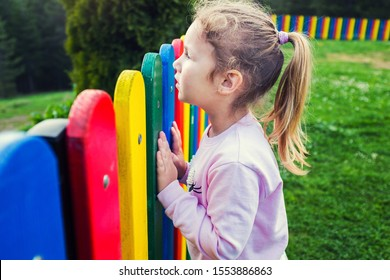 Little caucasian blonde girl looking over a rainbow colored picket fence, curious to see what's on the other side, shot from the child's side, profile view