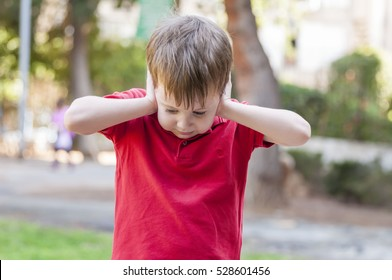 Little Caucasian boy closing ears with his hands in a protective position. Childhood traumatic experience, psychology, psychological, asperger syndrome, asperger's disorder, autistic, autism.